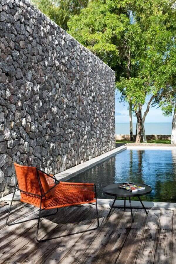 O revestimento de parede externa da área da piscina foi feita com pedra natural cinza. Fonte: Pinterest