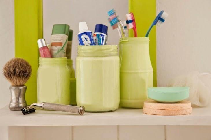Potes de vidro verdes com escovas e pastas de dente Foto de Kza Organizada