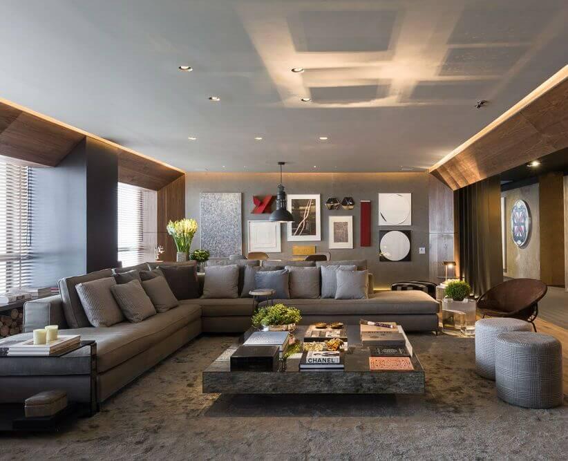 Sala ampla com sofá em L e mesa de centro com livros e objetos de decoração Projeto de Triplex Arquitetura