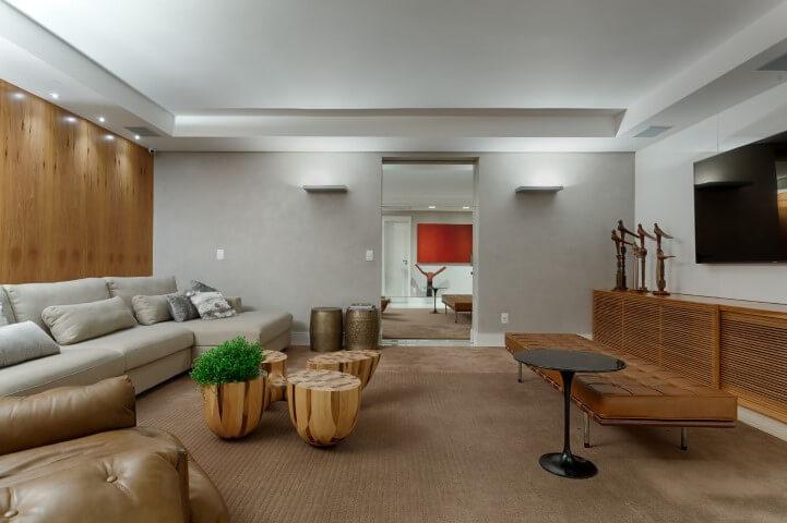 Sala de TV com decoração aconchegante, sofá em L claro e demais móveis em tons de marrom e madeira Projeto de Jaqueline Frauches