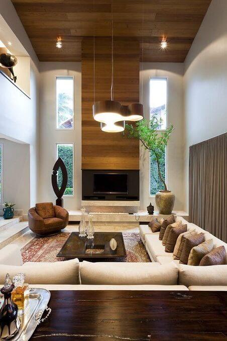Sala de TV com pé direito duplo e sofá em L com várias almofadas Projeto de Marlúcia Landim Decor