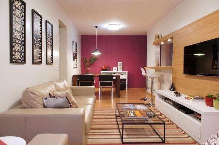 Sala de TV com sofá de couro claro Projeto de Lay Santos