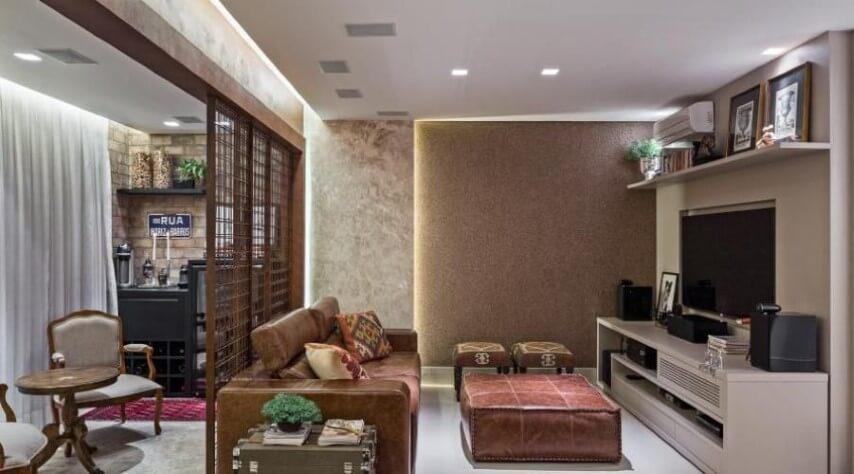 Sala de TV com sofá de couro marrom claro e puff do mesmo material Projeto de Leticia Hammerschmidt
