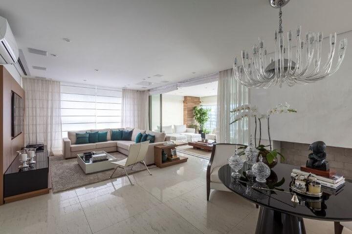 Sala de TV com sofá em L bege com almofadas verdes Projeto de Luciana Tomas