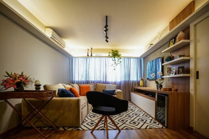 Sala de TV com sofá em L bege e painel de TV de madeira Projeto de Gabriela Toledo