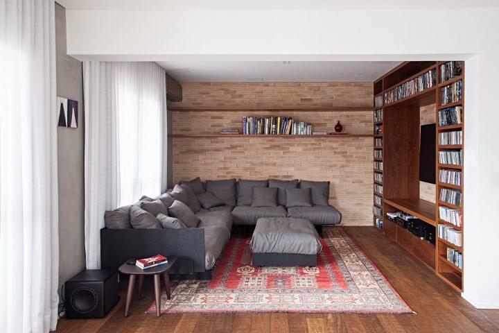Sala de TV com sofá em L cinza com puff central combinando Projeto de Korman Arquitetos