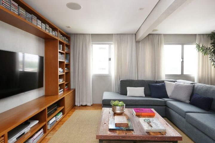 Sala de TV com sofá em L cinza e estante de madeira Projeto de Oliveira Arquitetura