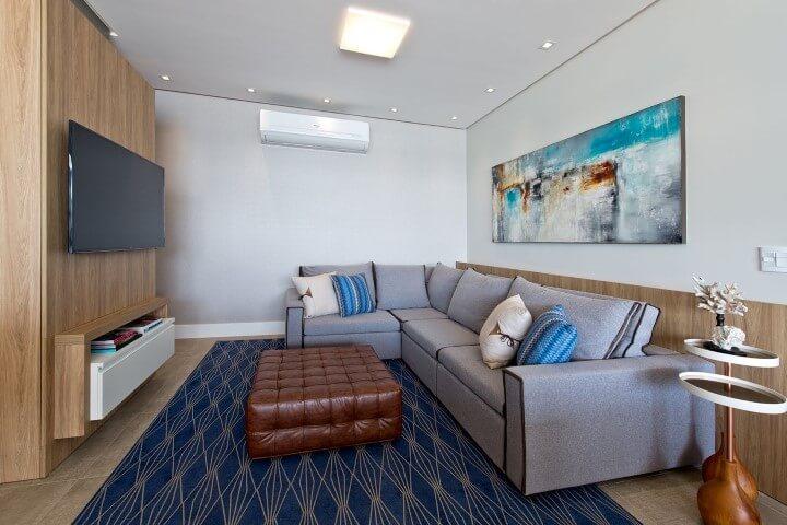 Sala de TV com sofá em L cinza e puff de couro no centro Projeto de Espaço do Traço
