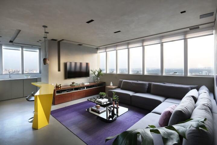 Sala de TV com sofá em L cinza e tapete roxo Projeto de Box 14