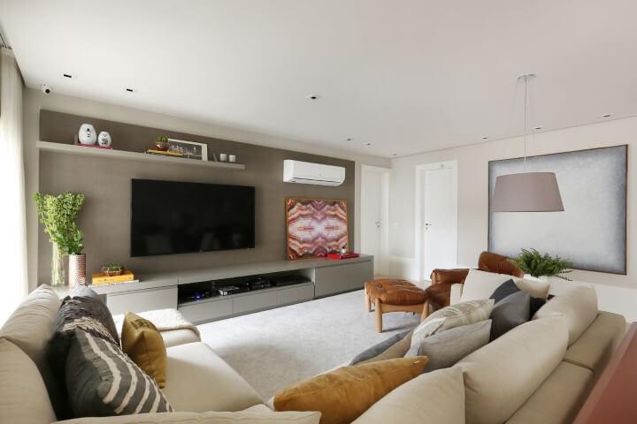 Sala de TV com sofá em L claro e almofadas diversas Projeto de Karen Pisaca