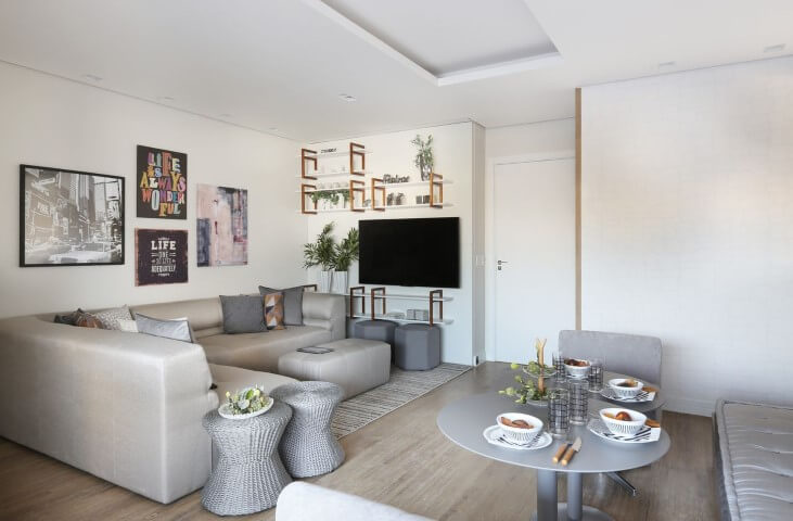 Sala de TV com sofá em L e puff central combinando e quadros decorativos Projeto de Lucia Wjuniski