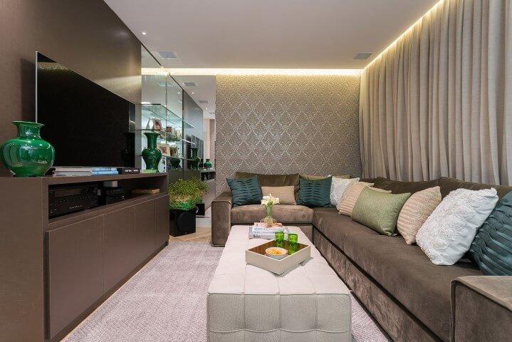 Sala de TV com sofá em L escuro combinando com rack marrom Projeto de Helena Koki