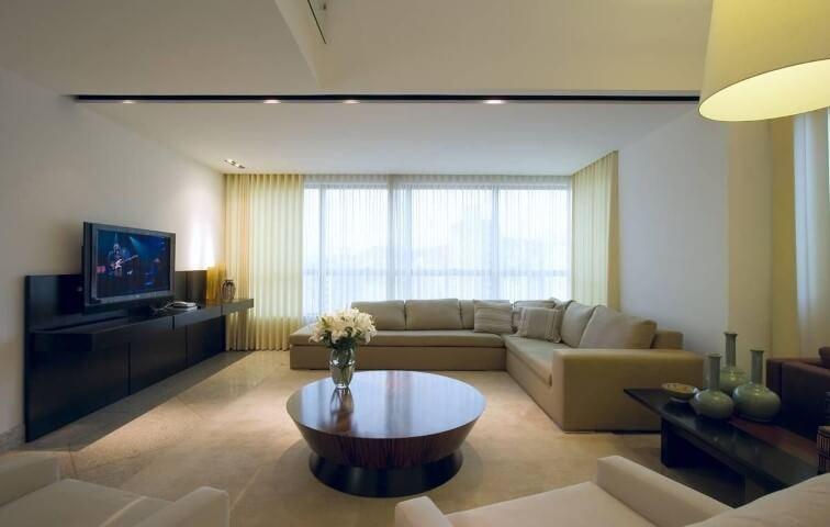 Sala de TV em sofá em L bege e poltronas claras Projeto e Renata Basques