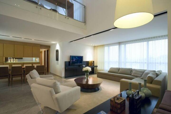 Sala de TV em sofá em L bege e poltronas claras Projeto e Renata Basques1