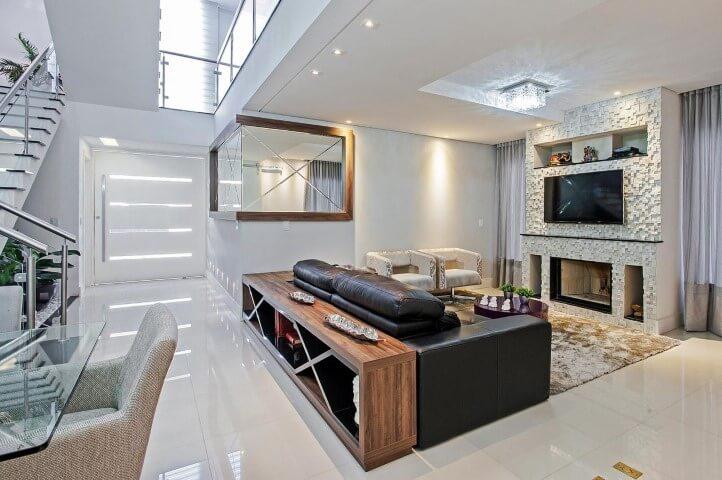 Sala de TV integrada com sofá de couro preto e decoração clara Projeto de Patricia Azoni