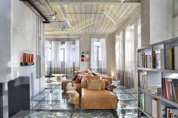 Sala de estar ampla com sofá de couro longo marrom bem claro Projeto de Gisele Taranto