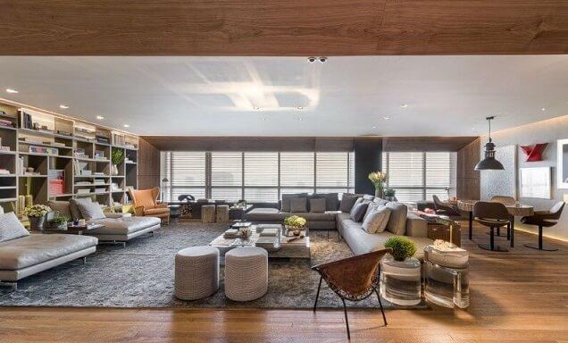 Sala de estar amplo com sofá em L cinza combinando com o tapete Projeto de Triplex Arquitetura