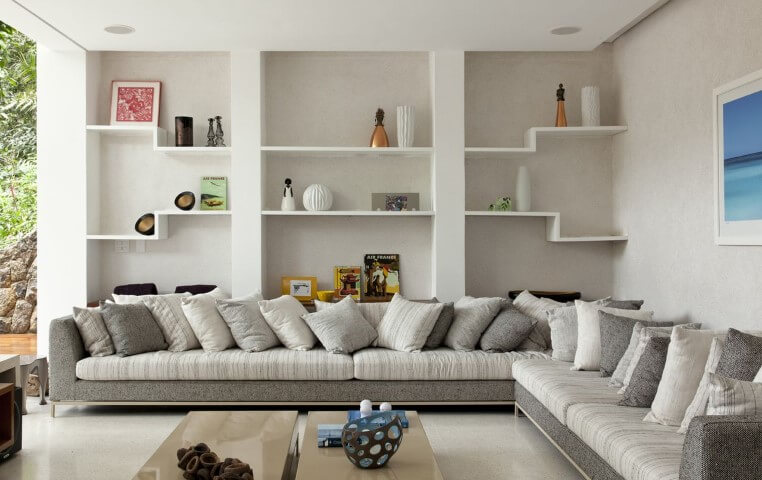 Sala de estar clean com sofá em L branco e cinza com almofadas combinando Projeto de Sandra Picciotto