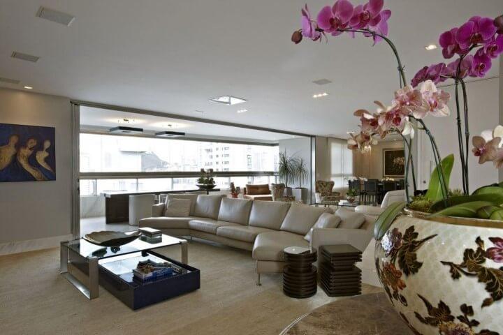 Sala de estar com decoração em tons claros com sofá de couro creme Projeto de Gislene Lopes