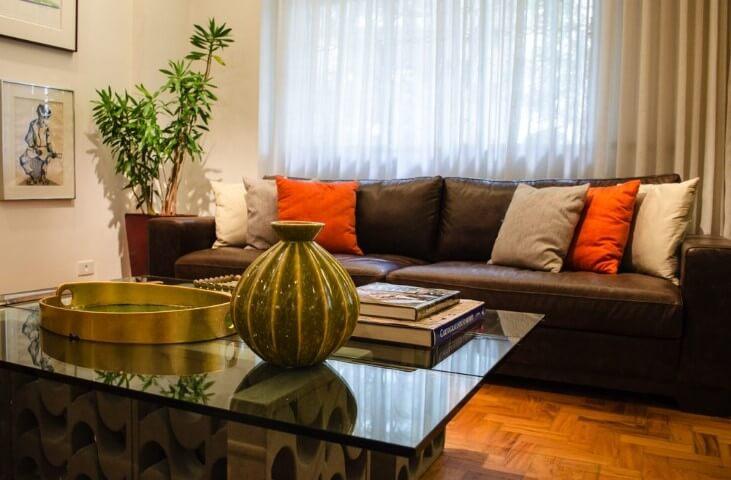 Sala de estar com mesa de centro de vidro com cobogós e sofá de couro marrom com almofadas Projeto de Adriana Fornazari