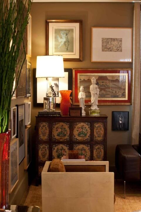 Sala de estar com molduras para quadros decorativos e vidro sobre as imagens Projeto de David Bastos