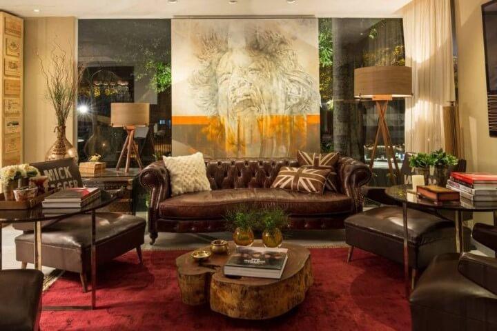 Sala de estar com poltronas e sofá de couro marrom Projeto de Casa Cor Paraguai