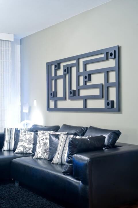 Sala de estar com quadro abstrato e sofá de couro preto com almofadas com estampas em preto e branco Projeto de Patricia Azoni