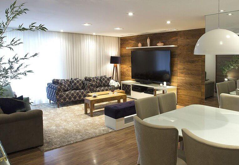 Sala de estar com rack branco e piso de madeira