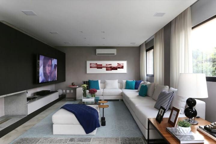 Sala de estar com sofá de canto branco e almofadas em tons de azul Projeto de Hildebrand Silva Arquitetura