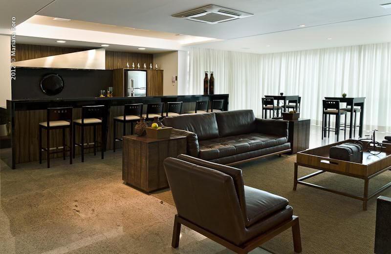 Sala de estar com sofá de couro e móveis de madeira Projeto de Rico Mendonça