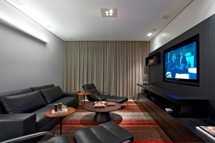Sala de estar com sofá de couro e poltronas do mesmo material Projeto de Graziella Nicolai