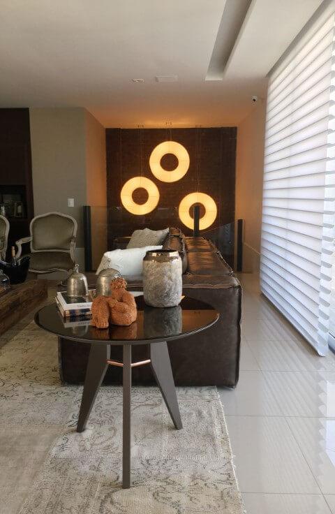 Sala de estar com sofá de couro escuro e almofadas brancas Projeto de Juliana de Sá