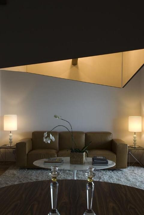 Sala de estar com sofá de couro marrom claro com abajures dos lados Projeto de Arq Donini
