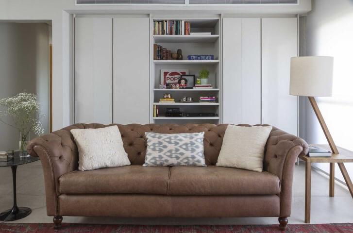 Sala de estar com sofá de couro marrom claro e pés redondos Projeto de Ana Yoshida