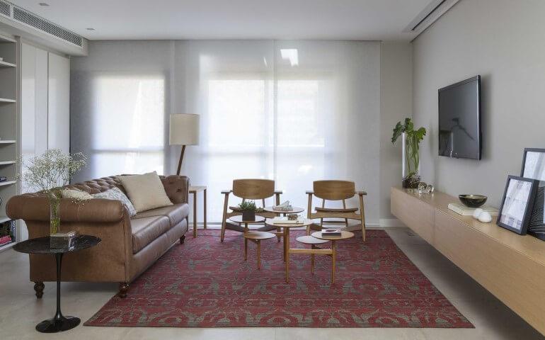 Sala de estar com sofá de couro marrom claro e tapete estampado Projeti de Ana Yoshida