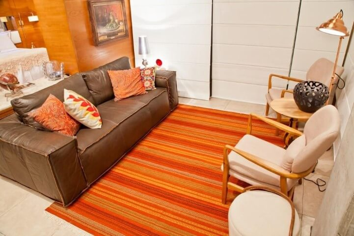 Sala de estar com sofá de couro marrom com almofadas combinando com o tapete Projeto de Rico Mendonça