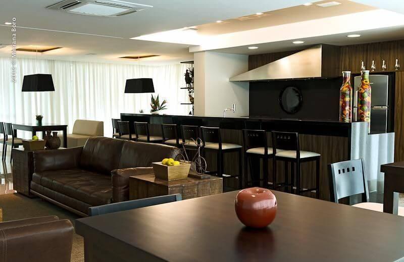 Sala de estar com sofá de couro marrom com cozinha integrada Projeto de Rico Mendonça