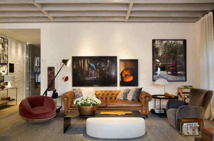 Sala de estar com sofá de couro marrom com poltronas de veludo Projeto de Paola Ribeiro