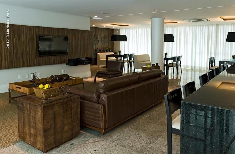 Sala de estar com sofá de couro marrom combinando com os tons de marrom da decoração Projeto de Rico Mendonca