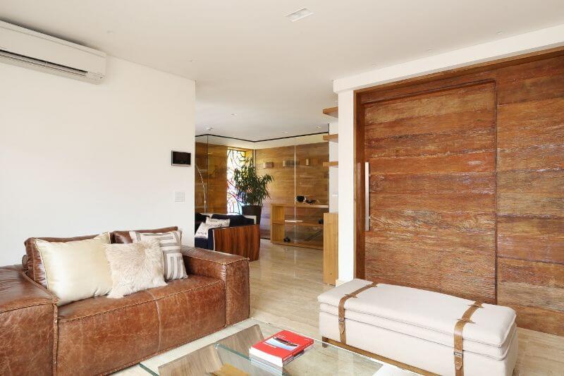 Sala de estar com sofá de couro marrom e almofadas claras Projeto de Studio BR