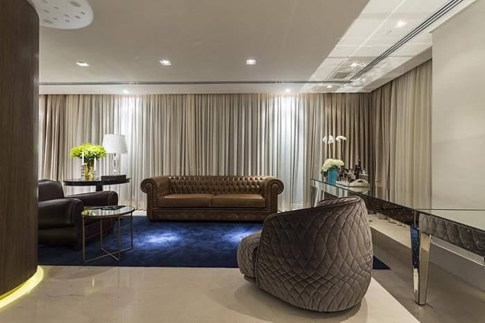 Sala de estar com sofá de couro marrom e poltronas grandes Projeto de Mauricio Karam