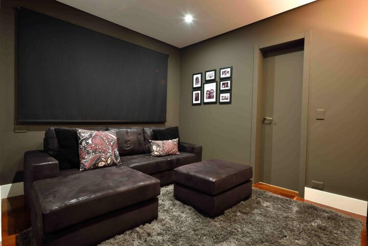 Sala de estar com sofá de couro marrom escuro e tapete felpudo Projeto de Rafael Guimarães