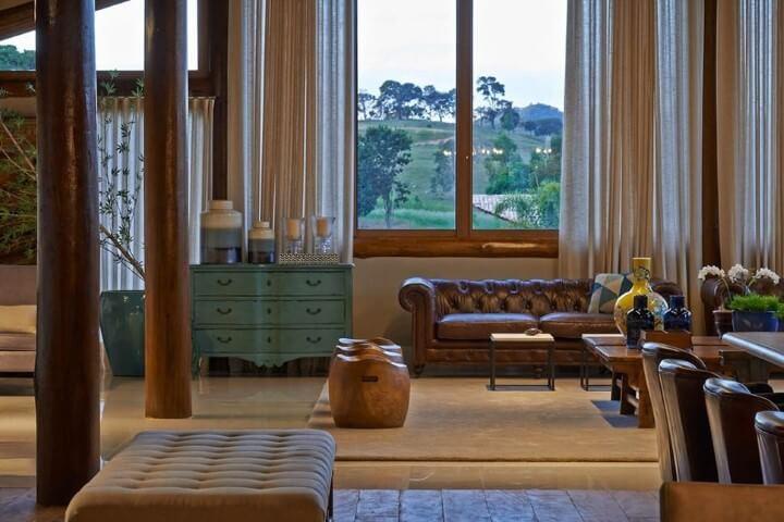 Sala de estar com sofá de couro marrom estilo capitonê Projeto de Glaucia Britto