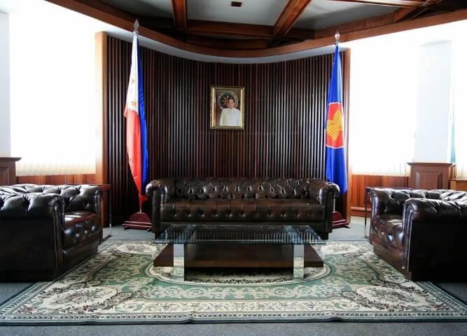 Sala de estar com sofá de couro marrom sintético combinando com poltronas Projeto de Juliana Pippi