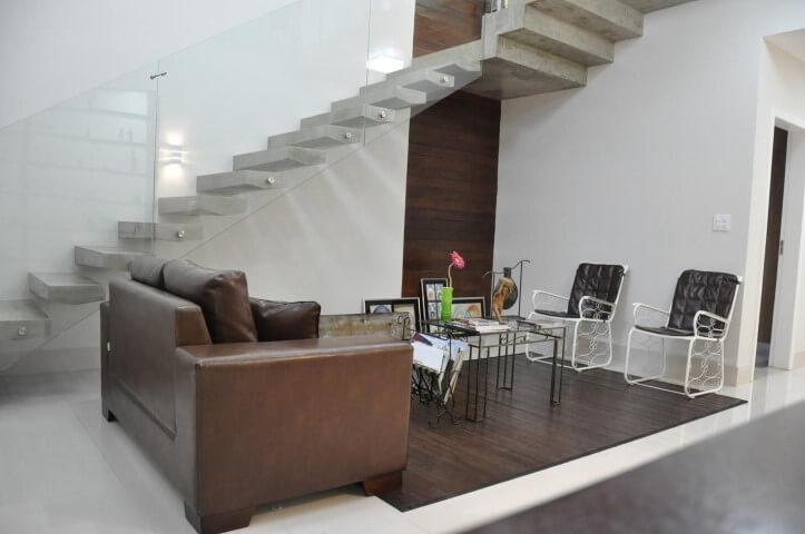 Sala de estar com sofá de couro pequeno marrom claro com cadeiras brancas Projeto de Pedro Haruf