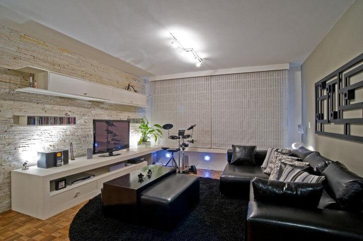 Sala de estar com sofá de couro preto com chaise Projeto de Patricia Azoni