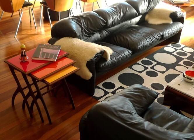 Sala de estar com sofá de couro preto com mantas de pele Projeto de Desmobilia