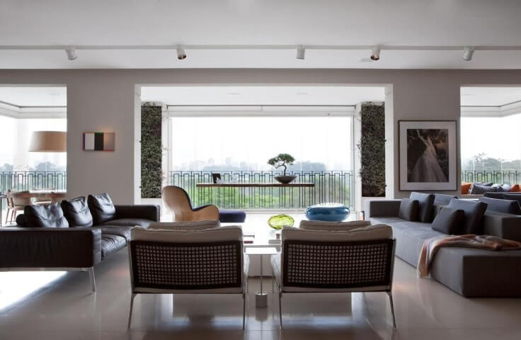 Sala de estar com sofá de couro preto com pés de metal Projeto de Patricia Martinez