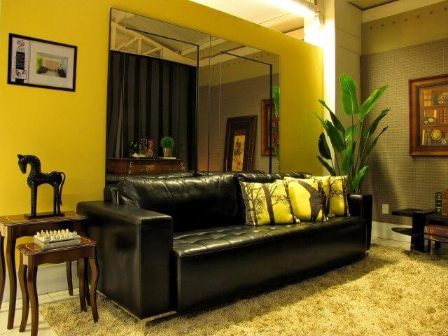 Sala de estar com sofá de couro preto e almofadas preto e brancas Projeto de Symon Hilgemberg Santos