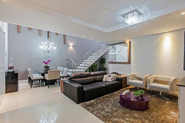 Sala de estar com sofá de couro preto e poltronas claras Projeto de Patricia Azoni